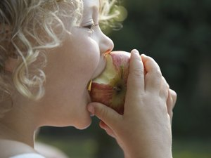 """""""Girl (3-5) biting into apple, profile, close-up"""""""