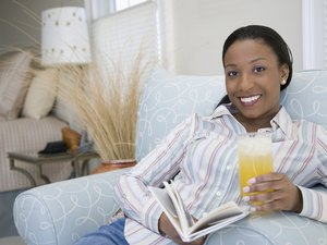 Portrait of a young woman holding a glass of juice and smiling