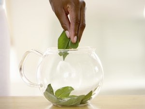 Person placing leaves into glass teapot, close up