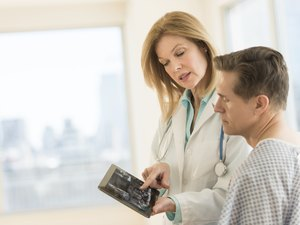 Doctor showing digital tablet to patient in clinic