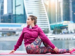 Young attractive woman practicing yoga, sitting in Half lord of the fishes exercise, Ardha Matsyendrasana pose, working out wearing pink sportswear, outdoor full length, modern urban city background