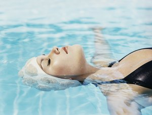 Young Woman Lying Afloat in a Swimming Pool With Her Eyes Closed