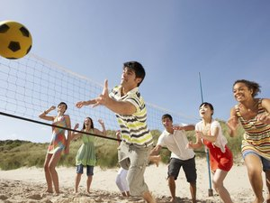 Teenage Friends Playing Volleyball On Beach