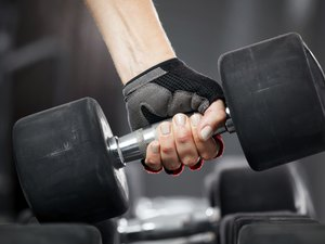 Rrack with metal dumbbells in gym.
