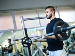 Muscular Bodybuilder Men Doing Exercises with Dumbbells in Gym