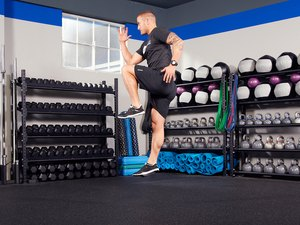 Man performing knee drive warm-up exercise