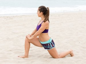 Woman stretching before her beach workout