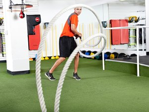 Man using the battle ropes during a workout at his gym
