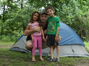 Clint poses with his children during a camping trip.