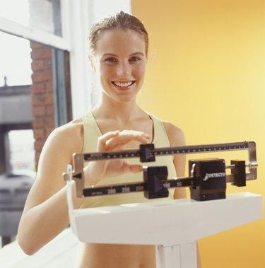 Woman weighing herself, adjusting scales