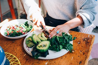 Woman chopping salad and avocados on a plate.
