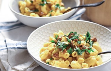 Two white bowls of butternut squash macaroni and cheese.