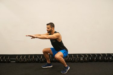 Man demonstrating how to do offset stance body-weight squats