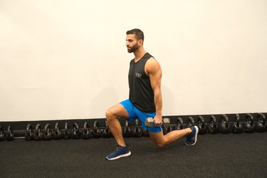 Man demonstrating how to do single dumbbell reverse lunges