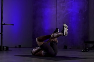 Woman demonstrating how to do the figure 4 stretch as part of a mobility workout
