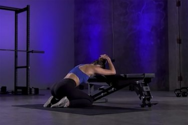 Woman demonstrating how to do a T spine stretch as part of a mobility workout