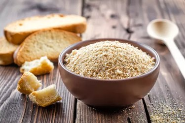 Bread on wood and breadcrumbs in bowl for gluten-free alternatives