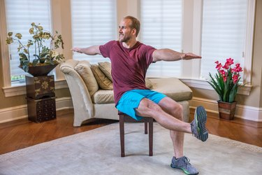 Man doing a seated abdominal twist exercise during a full-body chair workout