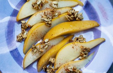 Top view of poached pears with candied sunflower seeds and cinnamon