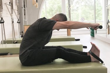 man performing pilates roll up