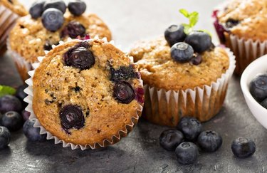 Blueberry-Banana Protein Muffins on table with scattered blueberries