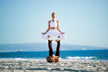Woman sitting in a meditative position on partner's feet on the beach.