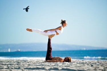 Woman performing back extension on partners feet on the beach.