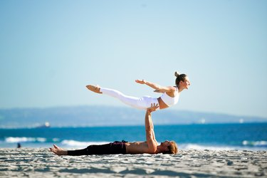 Woman performing back extension on partner's hands.