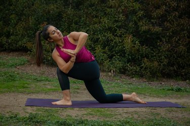 Woman performing twisting low lunge on yoga mat.