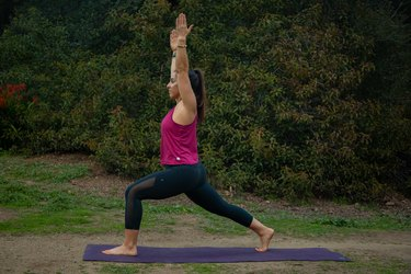 Woman performing high lunge on yoga mat.