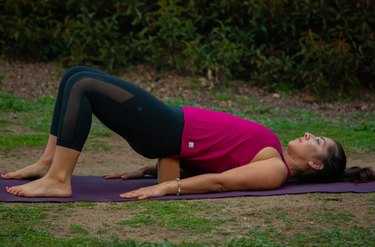 Woman lying on back with hips on yoga block for supported bridge pose.