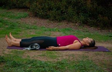 Woman lying in savasana outdoors.
