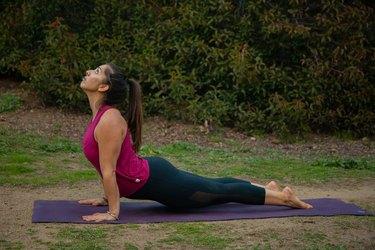Woman performing upward facing dog yoga pose.
