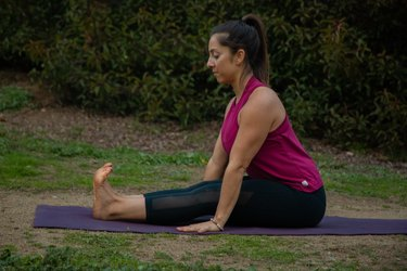 Woman stretching hamstrings in a seated position.
