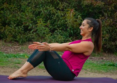Woman performing core exercise outdoors.