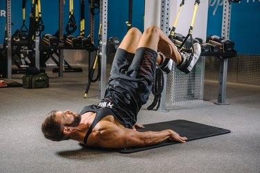Man demonstrating how to do TRX Hip Raises