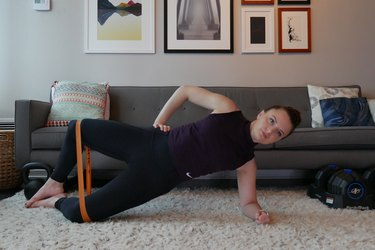Woman demonstrating how to do a banded side plank to clam shell