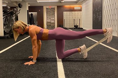 fitness instructor kira stokes demonstrates the Straight-Leg Donkey Kick glute exercise with a resistance band