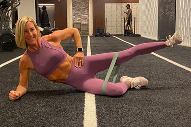 fitness instructor kira stokes demonstrates the Side-Lying Abduction glute exercise with a resistance band