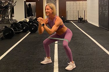fitness instructor kira stokes demonstrates the Squat With Glute Medius Activation glute exercise with a resistance band