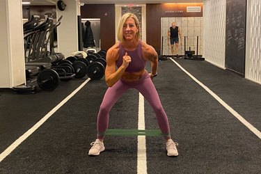 fitness instructor kira stokes demonstrates the Squat to Step-Out glute exercise with a resistance band