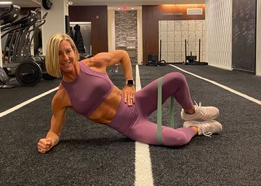 fitness instructor kira stokes demonstrates the clamshell glute exercise with a resistance band