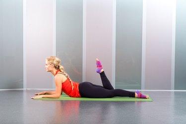 Woman doing Pilates exercise single-leg kick