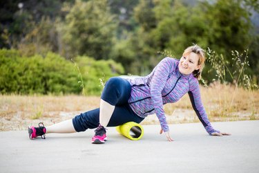 middle-aged woman doing foam rolling on her hip outdoors