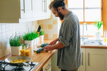 man in kitchen cooking sustainably