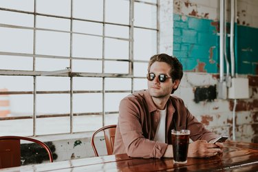 man drinking coffee indoors