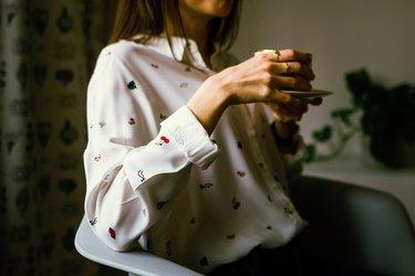 woman wearing blouse drinking tea