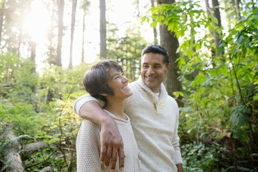 smilling woman and man in lush forest hiking