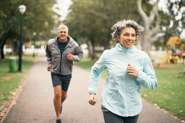 Woman and man who may want to get a flat stomach jogging outside