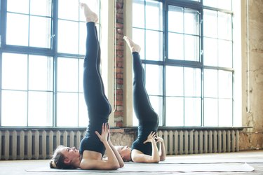 Women doing supported shoulderstand yoga pose for balance
